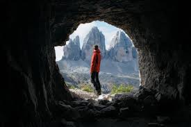 Man-Standing-At-Cave-Entrance