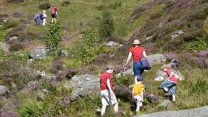 family-climbing-over-boulders-on-a-hike
